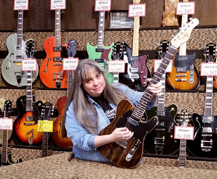Amy at Arthur's Music Store with a Michael Kelly 1950s Ebony electric guitar