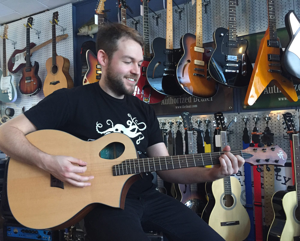 John Harney at Collar City Guitars playing a Michael Kelly Acoustic Port guitar