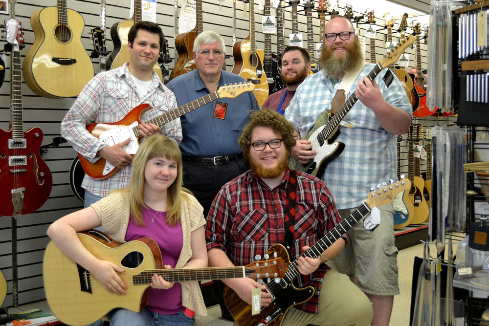 King Music Inc staff holding Michael Kelly electric guitars and acoustic guitars
