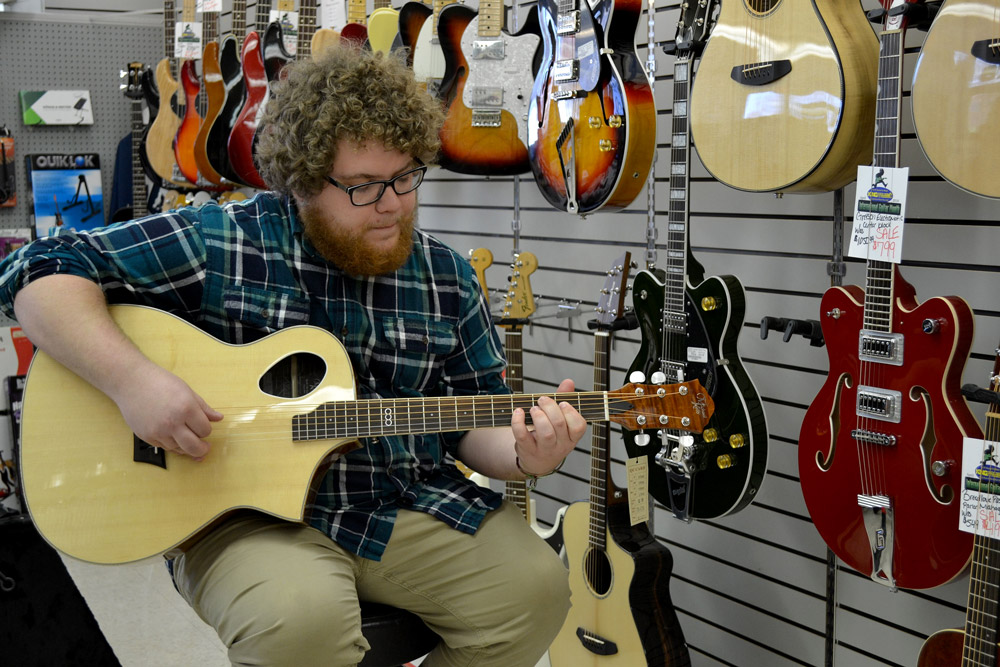 Bob from King Music Inc holding a Michael Kelly Triad Port acoustic guitar