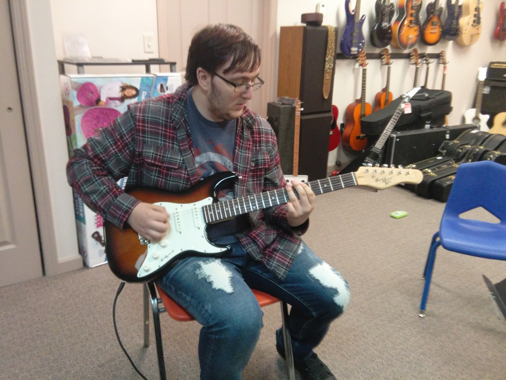 Student learning to play guitar at Robert Putt Studios on a Michael Kelly 1960s electric guitar.